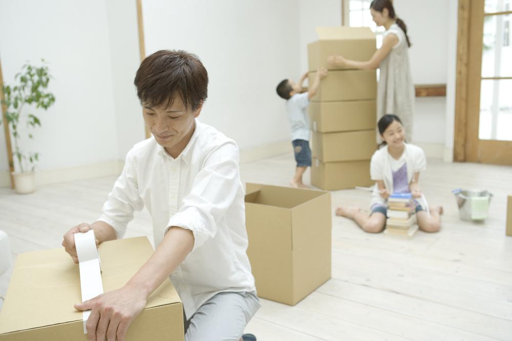 引越しの荷物の梱包をしている家族
