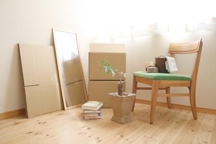 ダンボール、椅子、姿見、本などが置いてある部屋
