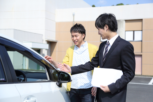 車の査定額を交渉する男性と買取り業者のスタッフ