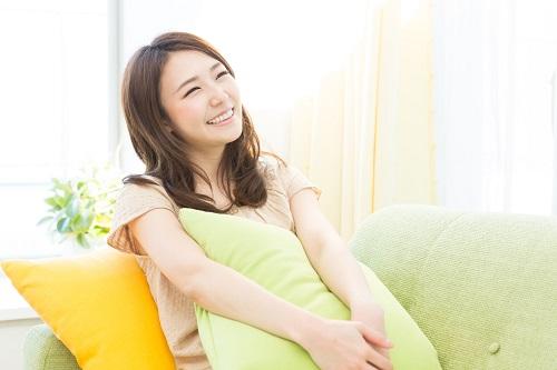 ソファに座って笑う女性
