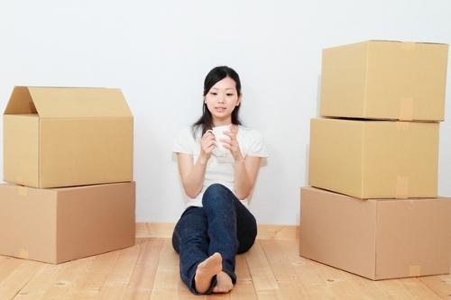 ダンボール箱に挟まれて座りながらコーヒーを飲む女性